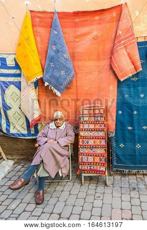 Marrakesh Morocco - December 8 2016: Local seller offers textile souvenirs in souks in Marrakesh Morocco Africa.