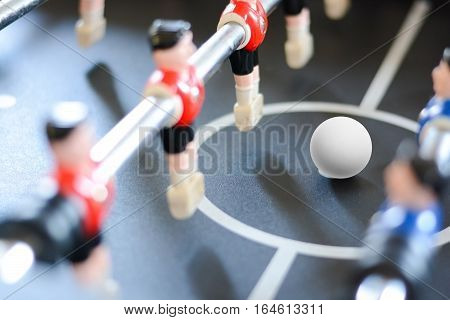 Football table game players suggesting team coaching