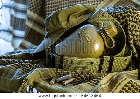 Compilation of Military Flask cap and ALICE belt lying on olive shemagh with ammunition cartridges