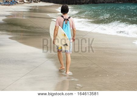 Back Shot Of Fashionable Surfer With Blue Bag Carrying His White Surf Board, Walking Along Beach And