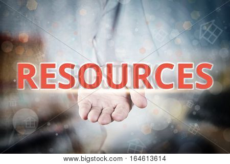 Man Hand Holding Resources Text On Blurry Home Icon Property Background.