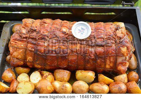 Cooked roast of pork or Italian porchetta recipe on a grill