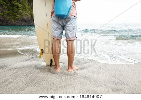 Cropped Rear Shot Of Barefooted Surfer In Jeans Shorts Standing On Wet Sand In Front Of Ocean, Enjoy