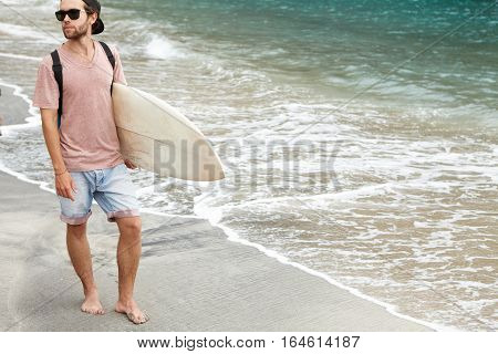 Outdoor Shot Of Fashionable Young Bearded Man In Shades Carrying His White Surfboard In His Hand, He