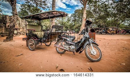 Siem Reap, Cambodia - December 07, 2015: A tuk tuk parked outside Ta Prohm temple at Angkor Archaeological Park of Siem Reap in Cambodia