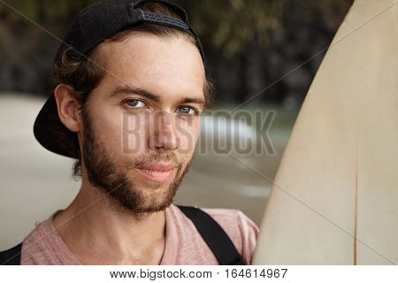 Close Up Portrait Of Young Handsome Winner Of Surf Contest, Looking At Camera With Sly Satisfied Smi