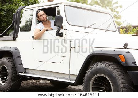 Stylish Young Caucasian Man Looking Out Open Window Of His White Sports Utility Vehicle. Unshaven Ma