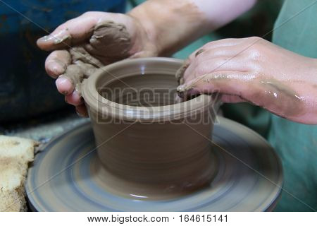 hands of a potter, creating an earthen jar on a pottery wheel