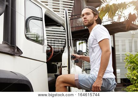Outdoor Portrait Of Stylish Bearded Man In Jeans Shorts Getting Into His White Sports Utility Vehicl