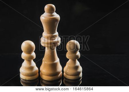 Chess pieces of wood - a queen and pawns. Wooden figures on a black background