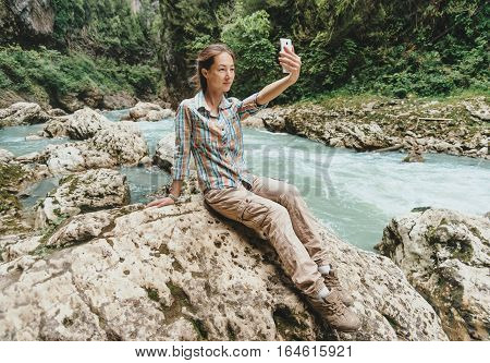 Traveler young woman sitting on stone and doing self-portrait with smartphone near the mountain river