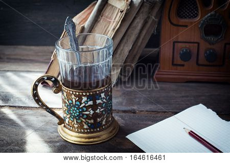 Still life with tea and old books and a piece of paper with a pencil