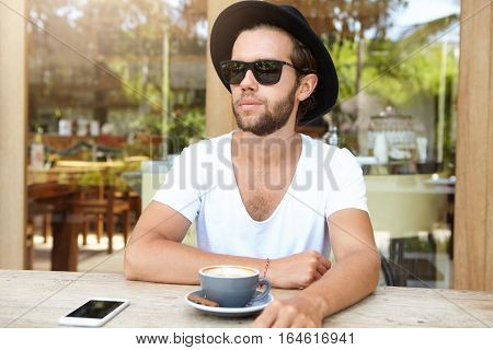 Fashionable Young Man In Trendy Sunglasses And White V-neck Shirt Having Rest At Sidewalk Cafeteria,