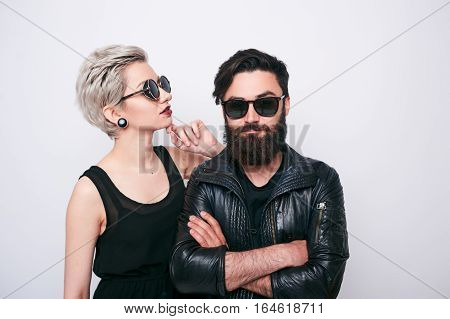 Young alternative couple in rock style clothes wearing black sunglasses over white background. Bikers culture. Young woman and bearded man