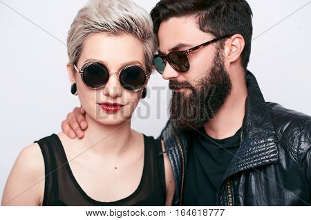 Closeup portrait of bearded young man and blond woman wearing sunglasses. Stylish couple in biker vintage clothes on white background. Fashion alternative concept