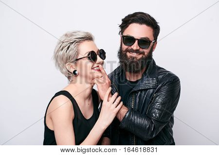 Hipster love concept. Stylish fashion couple in trendy fashionable clothes in studio over white background
