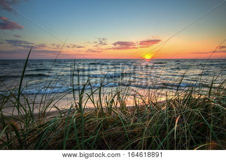 Tranquil Sunset Beach Background.  Beautiful sunset horizon over water with a sandy beach and dune grass in the foreground. Hoffmaster State Park. Muskegon, Michigan poster