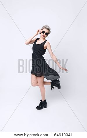 Vertical portrait of a stunning blond young woman wearing black dress and retro round sunglasses over white background. Fashion girl in stylish rock clothes. In motion concept