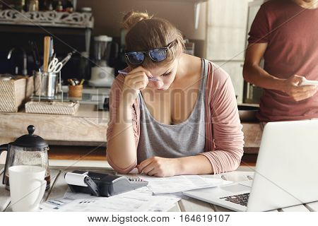 Depressed Couple Facing Credit Problem. Stressed Wife Looking Exhausted While Doing Accounts At Home
