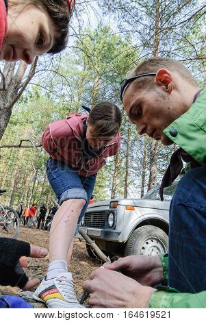 Subbotino, Russia - April 20, 2008: Samogon festival of cyclists in forest. The male physician gives first aid to the girl who was traumatized on exercise. Tyumen region