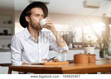 Young Hipster Wearing Black Hat And White Shirt Drinking Tea Or Coffee And Typing Message On Generic