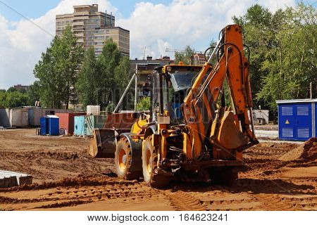 Tractor works on construction site with many sand at summer sunny day