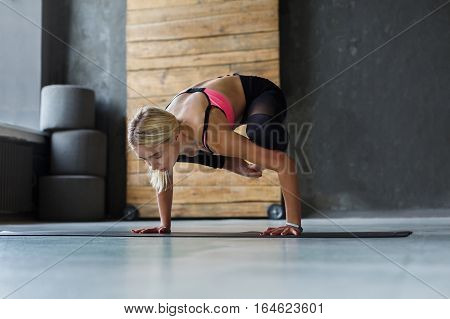 Young slim blond woman in yoga class making asana exercises. Girl do crane pose. Healthy lifestyle in fitness club. Stretching, hand stand balance