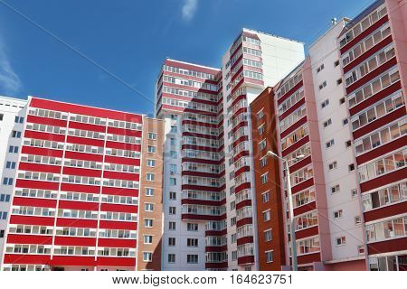Part of pink residential building with many red loggias at summer day
