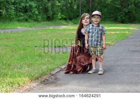 Little handsome boy and his young mother pose in park at sunny day