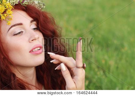 Woman in wreath looks on ladybird on finger up on meadow at summer