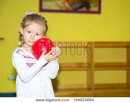 Little child girl playing with ball in kindergarten in Montessori preschool Class. Adorable kid in nursery room.