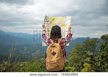 Women traveler with backpack checks map to find directions in wilderness area