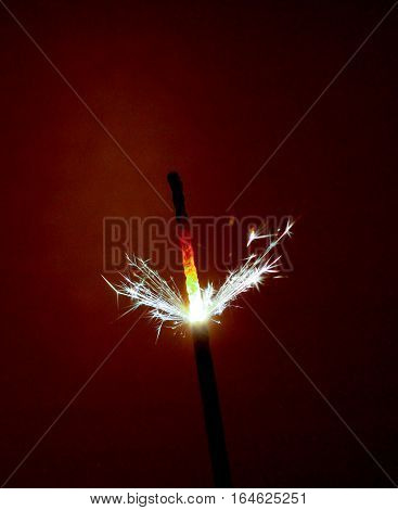 picture of a party sparkler on dark brown background