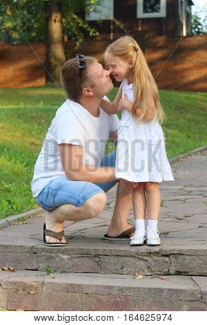 Happy father and his little daughter rub noses in summer sunny park