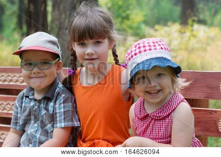 Happy little boy and two girls sit on bench and smiles at sunny summer day