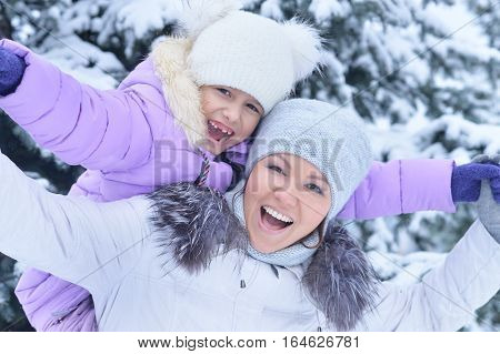 happy mother and daughter, posing outdoors in winter