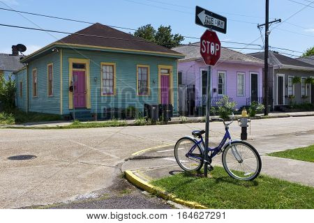 New Orleans Louisiana USA - June 17 2014: One bicycle parket at a stop sign in front of a row of colorful houses in a street of the city of New Orleans in Louisiana.