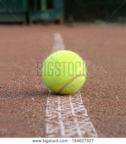 Front view of yellow tennis ball lays on ground outdoor court marking line closeup
