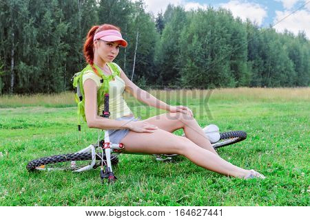 Slender girl with a backpack sits on a recumbent bike on the grass on a warm day