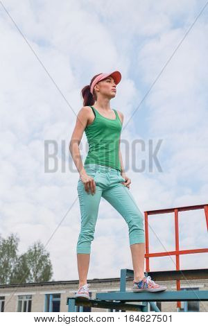 Beautiful sporty girl is on the bar on the street on the background of beautiful cloudy sky