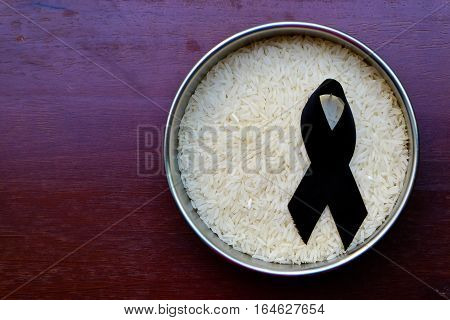 Black mourning ribbon on the rice on the table