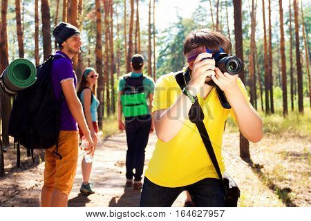 Young tourists walking through the wood path. Guy taking photos with the camera