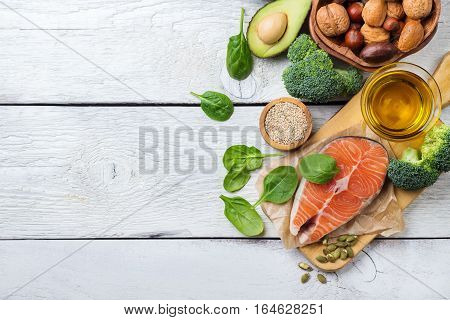 Selection of healthy fat sources food, salmon fish avocado olive oil pumpkin seeds nuts broccoli green spinach on a white rustic wooden table. Copy space background, top view, flat lay overhead