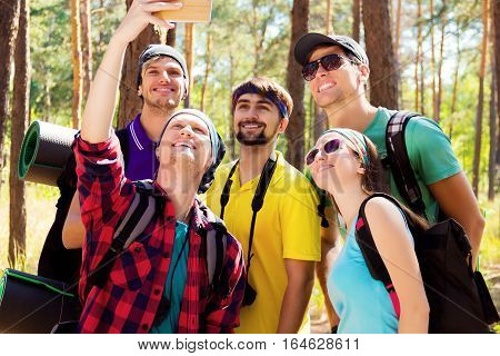 Young tourists taking selfie with the smartphone in the woods