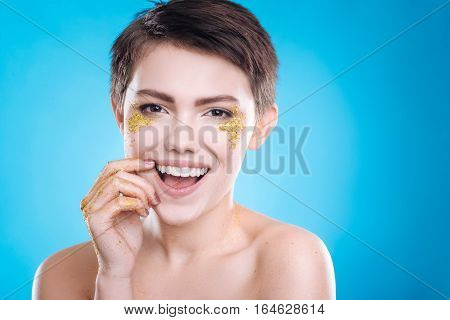 Breath of youth. Cheerful content beautiful model lookign at you and smiling while posing isolated on blue background