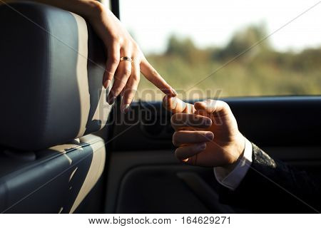 Just a touch - fingers of newlyweds touch in the lights of the sun in car