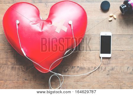 red broken heart with bandage listening to music on mobile phone Broken heart concept on wood floor