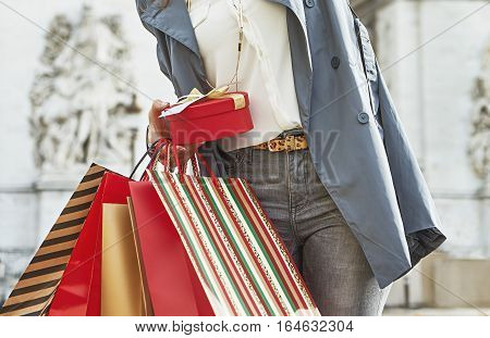 Stylish Christmas in Paris. trendy woman in trench coat with shopping bags and Christmas present in Paris France l