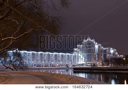 Nightly landscape of skyscrapers near river. Minsk city center view and Svislach river in the evening. Night Scene Trinity Hill In Minsk Downtown Nemiga Nyamiha Belarus. View With Svisloch River Belarus.