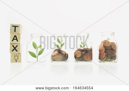 tax message on wood block stacking gold coins business finance and money concept.